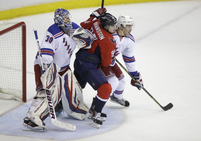 New York Rangers goalie Henrik Lundqvist, left, and New York Rangers defenseman Ryan McDonagh, right, defend Washington Capitals center Marcus Johansson (90) during the third period of Game 2 of a Stanley Cup NHL playoff hockey series on Saturday, May 4, 2013, in Washington. (AP Photo/Evan Vucci)