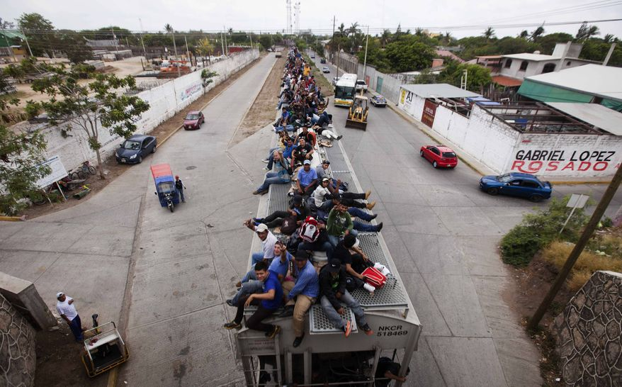 ** FILE ** Migrants ride on top of a northbound train toward the U.S.-Mexico border in Juchitan in southern Mexico on Monday, April 29, 2013. Migrants crossing Mexico to get to the U.S. have increasingly become targets of criminal gangs who kidnap them to obtain ransom money. (AP Photo/Eduardo Verdugo)