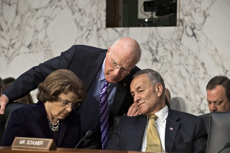 **FILE** Senate Judiciary Committee Chairman Patrick Leahy (center), Vermont Democrat, speaks with committee members and Democratic Sens. Charles Schumer (right) of New York and Dianne Feinstein of California on Capitol Hill in Washington on April 22, 2013, during the committee's hearing on immigration reform. (Associated Press)