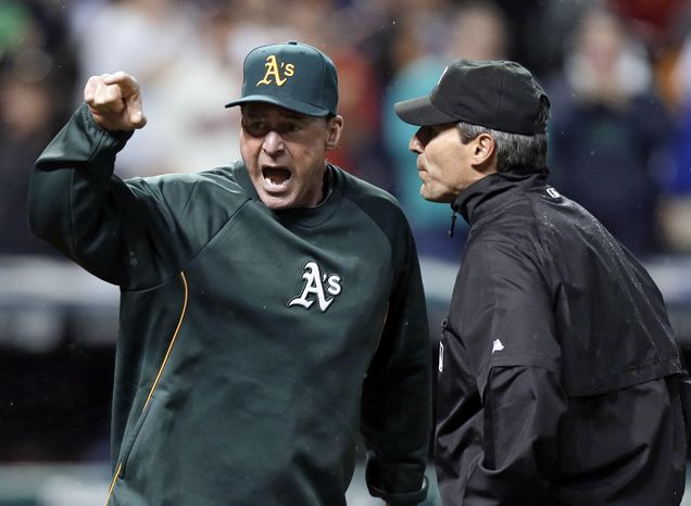 Oakland Athletics manager Bob Melvin, left, argues with umpire Angel Hernandez after a review failed to turn a double by Adam Rosales into a home run in the ninth inning of the A's baseball game against the Cleveland Indians on Wednesday, May