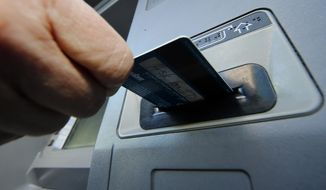 **FILE** A person inserts a debit card into an ATM machine in Pittsburgh on Jan. 5, 2013. (Associated Press)