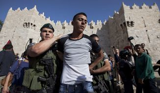 A Palestinian youth is detained by border police officers at the Damascus Gate as Israelis march celebrating Jerusalem Day, Wednesday, May 8, 2013, in Jerusalem's Old City. Jerusalem Day marks Israel's capture of east Jerusalem and the reunification of the city, which had been divided into Israeli and Jordanian sectors from Israel's establishment in 1948 until the 1967 war. (AP Photo/Sebastian Scheiner)