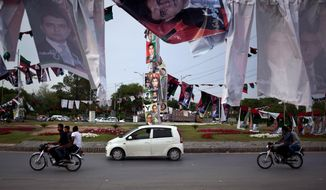 ** FILE ** Pakistani motorists ride past banners and posters of various candidates for upcoming elections, hanged with poles at a roundabout in Islamabad, Pakistan on Saturday, April 27, 2013. (AP Photo/Anjum Naveed)