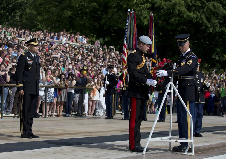 England's Prince Harry places a wreath with the help of a member of The Old Guard during a wreath-laying ceremony at theTomb of the Unknowns at Arlington National Cemetery in Arlington, Va., Friday, May 10, 2013. Standing left is Major Gen. Michael Linnington. (AP Photo/Carolyn Kaster)