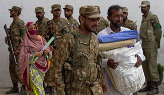 A Pakistani army soldier escorts election staff carrying ballots for the next day's elections in Islamabad, Pakistan, on May 10, 2013. (Associated Press)