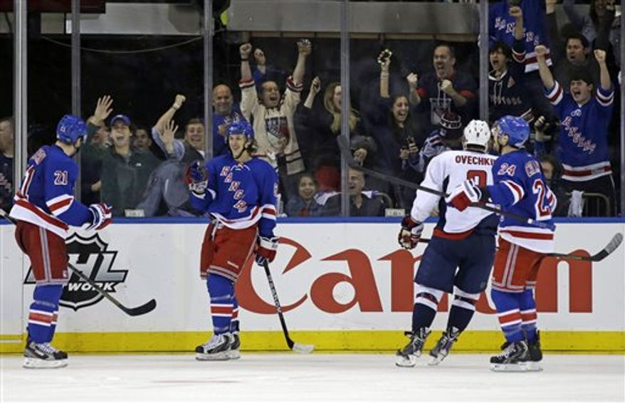 New York Rangers left wing Carl Hagelin (62), of Sweden, and right wing Ryan Callahan (24) celebrate with center Derek Stepan (21) after Stepan scored a goal as Washington Capitals left wing Alex Ovechkin (8), of Russia, skates past them in the third period of Game 4 of their first-round NHL Stanley Cup playoff series in New York, Wednesday, May 8, 2013. The Capitals won 4-3. (AP Photo/Kathy Willens)