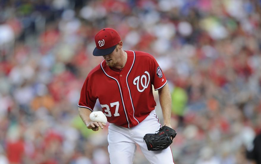 Stephen Strasburg takes a moment to use the rosin bag during a disastrous fifth inning in which an error by Ryan Zimmerman on the presumed third out became a debacle for the right-hander in the Nationals' loss to the Cubs. (Associated Press photo)
