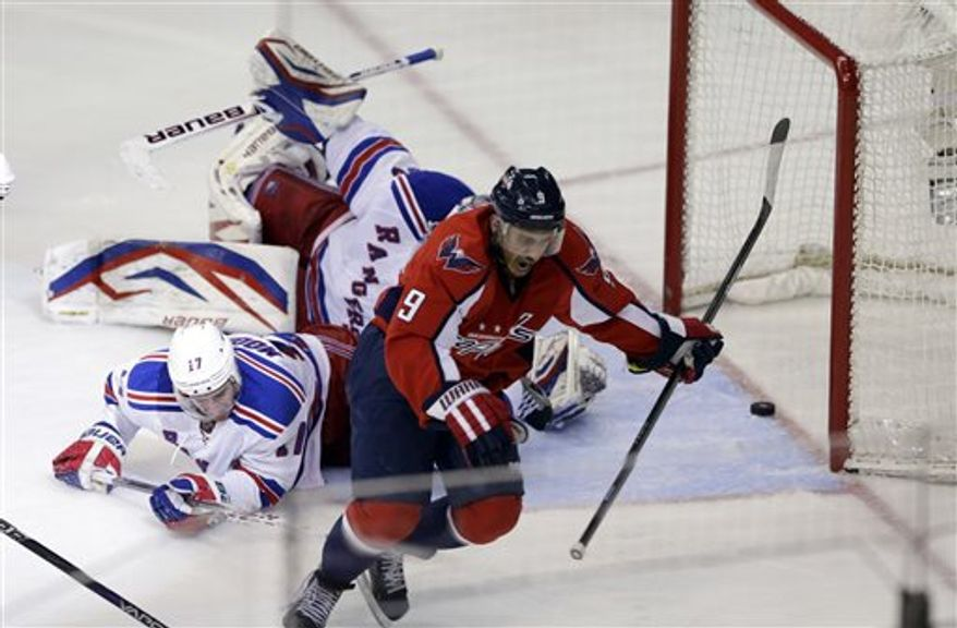 Washington Capitals center Mike Ribeiro (9) celebrates scoring the game-winning goal past New York Rangers goalie Henrik Lundqvist (30), from Sweden, with defenseman John Moore (17), in overtime of Game 5 first-round NHL Stanley Cup playoff hockey series, Friday, May 10, 2013, in Washington. The Capitals won 2-1, in overtime. (AP Photo/Alex Brandon)