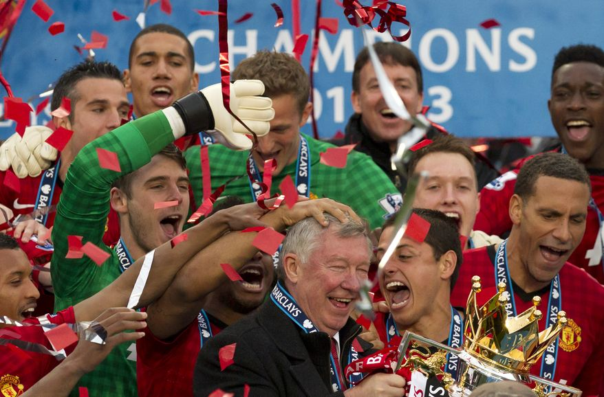 Manchester United's manager Sir Alex Ferguson, bottom centre, grasps the English Premier League Trophy as he celebrates with his team after his last home game in charge of the club, their English Premier League soccer match against Swansea, at Old Trafford Stadium, Manchester, England, Sunday May 12, 2013. (AP Photo/Jon Super)