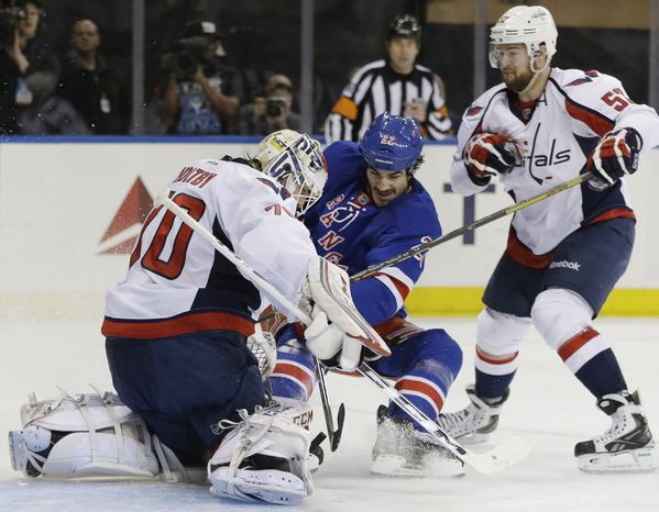 New York Rangers center Brian Boyle (22) takes a shot as Washington Capitals goalie Braden Holtby (70) defends and Washington Capitals defenseman Mike Green (52) looks on in the second period of Game 6 of their NHL Stanley Cup hockey playoff series in New York, Sunday, May 12, 2013. (AP Photo/Kathy Willens)