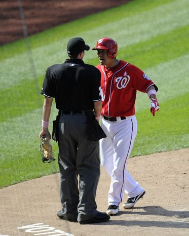 Washington Nationals' Kurt Suzuki, right, continues to argue with home plate umpire John Tumpane, left, after being ejected for arguing after being called out on strikes during the ninth inning of a baseball game against the Chicago Cubs, Sunday, May 12, 2013, in Washington. The Cubs won 2-1. (AP Photo/Nick Wass)