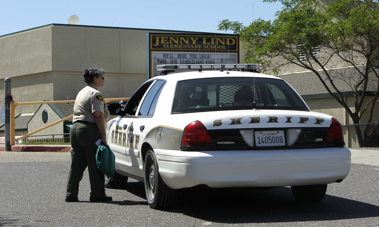 ** FILE ** Calaveras County sheriff's deputies and volunteers stand watch at the Jenny Lind Elementary School in Valley Springs, Calif., on Monday, April 29, 2013, after the murder of one its students over the weekend. A 12-year-old boy was arrested on Saturday, May 11, 2013, in the death of the student, who was his sister. (AP Photo/Rich Pedroncelli)
