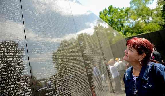Patty Thompson of West Palm Beach, Fla., looks up at the name of her husband, Spc. Raymond Clark Thompson who has been added to the wall of the Vietnam Veterans Memorial following a Mother's Day ceremony to honor Raymond and three other American servicemen who have been added to the wall, Washington, D.C., Sunday, May 12, 2013. (Andrew Harnik/The Washington Times)