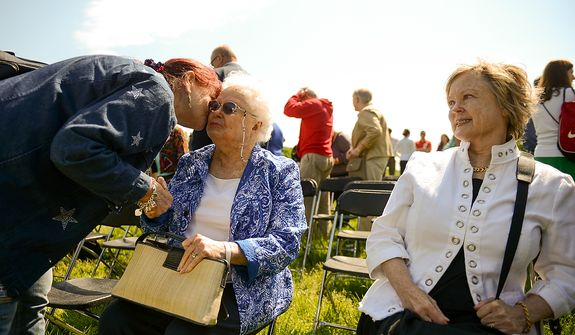 Patty Thompson of West Palm Beach, Fla., left, who's husband Spc. Raymond Clark Thompson has been added to the wall of the Vietnam Veterans Memorial, kisses Jeanette Lilly, the mother of 1st Lt. Lawrence Lilly who went missing in action in Vietnam, following a Mother's Day ceremony to honor Patty's husband  Raymond and three other American servicemen who have been added to the wall, Washington, D.C., Sunday, May 12, 2013. Also pictured is Jeanette's daughter, Susan Harvey of Alexandria, Va., right. (Andrew Harnik/The Washington Times)