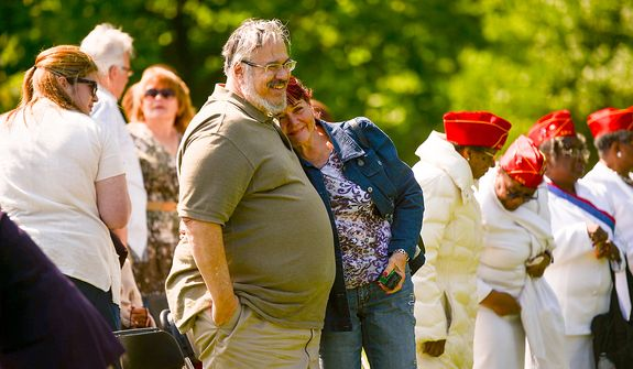 Patty Thompson of West Palm Beach, Fla., center, who's husband Spc. Raymond Clark Thompson has been added to the wall of the Vietnam Veterans Memorial, is comforted by her friend Martin Vesole of Del Ray Beach, Fla. at a Mother's Day ceremony to honor Raymond and three other American servicemen who have been added to the wall, Washington, D.C., Sunday, May 12, 2013. (Andrew Harnik/The Washington Times)