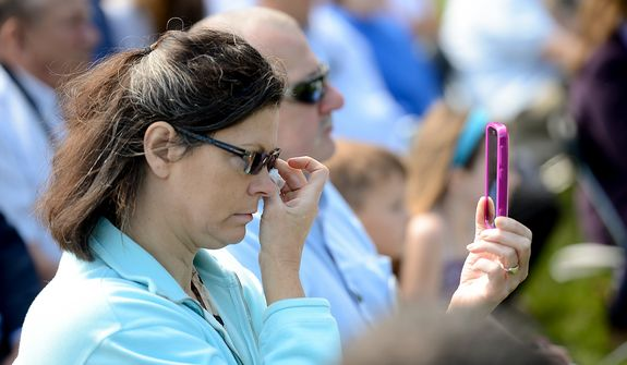 A woman in the audience wipes tears from her eyes during a Mother's Day ceremony to honor four American servicemen who have been added to the wall of the Vietnam Veterans Memorial, Washington, D.C., Sunday, May 12, 2013. (Andrew Harnik/The Washington Times)