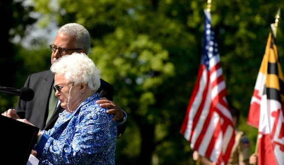 Master of Ceremony Harry Robinson, left, comforts Jeanette Lilly, the mother of MIA 1st Lt. Lawrence Lilly after she breaks down in tears while trying to speak about her son at a Mother's Day ceremony to honor four American servicemen who have been added to the wall of the Vietnam Veterans Memorial, Washington, D.C., Sunday, May 12, 2013. (Andrew Harnik/The Washington Times)