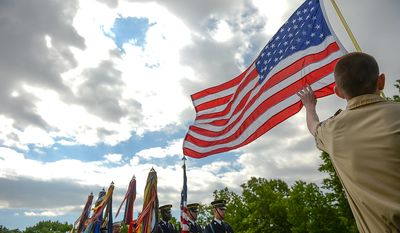 Boyscout Jim McCrery, 15, of Washington, D.C., right, holds an American Flag as members of the Joint Armed Forces Color Guard perform the presentation of the colors at a Mother's Day ceremony to honor four American servicemen who have been added to the wall of the Vietnam Veterans Memorial, Washington, D.C., Sunday, May 12, 2013. (Andrew Harnik/The Washington Times)