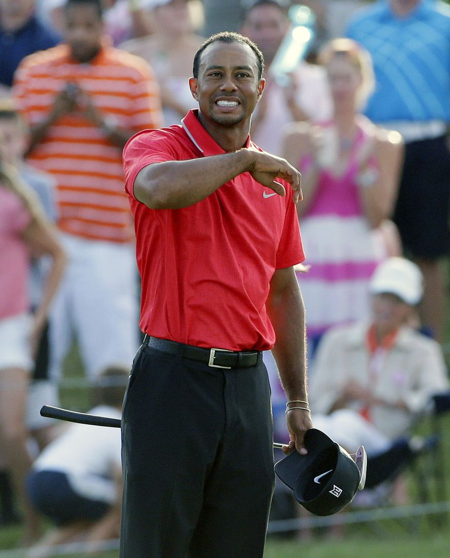 Tiger Woods pauses on the 18th green after winning The Players championship golf tournament at TPC Sawgrass, Sunday, May 12, 2013 in Ponte Vedra Beach, Fla. (AP Photo/Gerald Herbert)