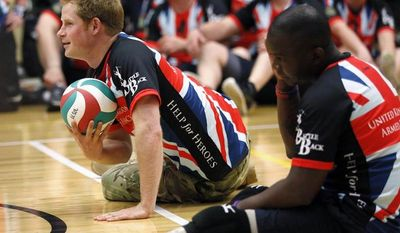 Britain's Prince Harry plays sitting volleyball with the United Kingdom team during a visit to the Warrior Games on Saturday, May 11, 2013, in Colorado Springs, Colo. The Warrior Games is a Paralympic-style competition featuring injured servicemen and women from the United States, United Kingdom, Canada and Australia. (AP Photo/Rick Wilking, Pool)