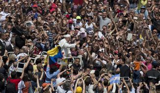Pope Francis waves to the crowd packed into St. Peter's Square at the Vatican on Sunday, May 12, 2013, after leading his first canonization ceremony. (AP Photo/Alessandra Tarantino)