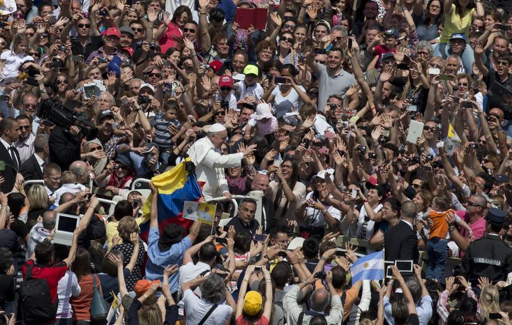 Pope Francis waves to the crowd packed into St. Peter's Square at the Vatican on Sunday, May 12, 2013, after leading his first canonization ceremony. (AP Photo/Ales