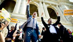 State Sen. D. Scott Dibble (left), sponsor of the gay marriage bill in the Minnesota Senate, and his partner Richard Leyva greet a crowd at the State Capitol. Gov. Mark Dayton said he will sign the bill as early as Tuesday. (Associated Press)