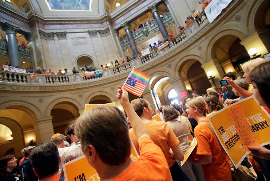 A gay-marriage proponent waves the U.S. flag and a rainbow flag Monday as supporters and opponents of Minnesota's gay-marriage bill gather in the State Capitol rotunda in St. Paul. The Legislature became the 12th to pass gay marriage, making the institution a sex-neutral union of two people. (Associated Press)