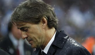 Manchester City's manager Roberto Mancini leaves the pitch after their loss to Wigan Athletic at the end of their English FA Cup final soccer match at Wembley Stadium, London, Saturday, May 11, 2013. (AP Photo/Jon Super)