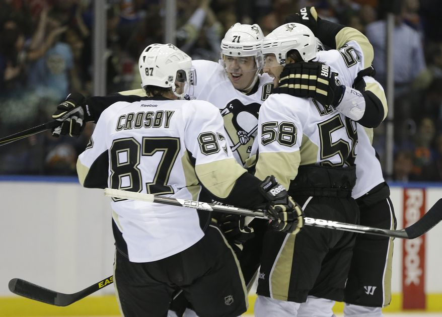 Pittsburgh Penguins center Sidney Crosby (87), defenseman Kris Letang (58) and Penguins center Evgeni Malkin (71) of Russia after Pittsburgh defenseman Paul Martin, scored the tying goal in the third period of Game 6 of their first-round NHL Stanley Cup playoff hockey series in Uniondale, N.Y., Saturday, May 11, 2013. The Penguins went on to win 4-3 in overtime on Brooks Orpik's goal. (AP Photo/Kathy Willens)