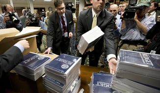 **FILE** Copies of President Obama's budget plan for fiscal year 2014 are distributed to Senate staff on Capitol Hill in Washington on April 10, 2013. (Associated Press)
