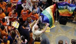 Thousands filled the Minnesota State Capitol as they waited for word that the Senate had passed the gay marriage bill Monday, May 13, 2013, in St. Paul, Minn. The governor has now signed the bill into law. (AP Photo/Jim Mone)