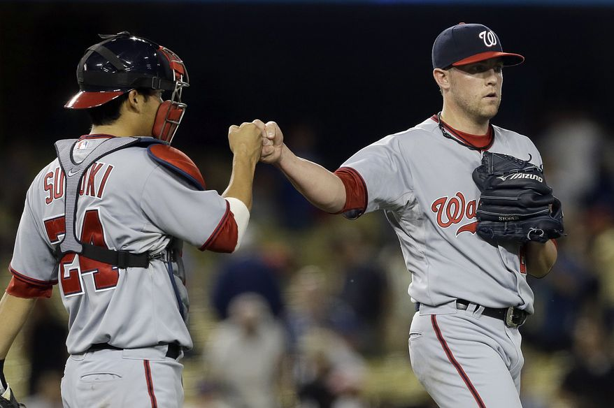 Washington Nationals closer Drew Storen and catcher Kurt Suzuki celebrate their win over the Los Angeles Dodgers in a baseball game in Los Angeles Monday, May 13, 2013. The Nationals won, 6-2. (AP Photo/Reed Saxon)