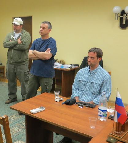 In this handout photo provided by the FSB, acronym for Russian Federal Security Service, a man claimed by FSB to be Ryan Fogle, right, a third secretary at the U.S. Embassy in Moscow, with Embassy officials at left, sits in the the FSB offices in Moscow, early Tuesday, May 14, 2013. Russia's security services say they have caught a U.S. diplomat who they claim is a CIA agent in a red-handed attempt to recruit a Russian agent. (AP Photo/FSB Public Relations Center)