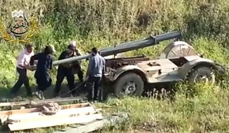 This image taken from video obtained from Ugarit News, which has been authenticated based on its contents and other AP reporting, shows Syrian rebels preparing to fire a rocket at Mannagh air base in Aleppo province, Syria, Monday, May 13, 2013. (AP Photo/Ugarit News via AP video)