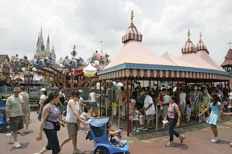 **FILE** Guests wait in long lines for the Dumbo ride at the Walt Disney World Magic Kingdom theme park in Lake Buena Vista, Fla., on May 17, 2007. (Associated Press)