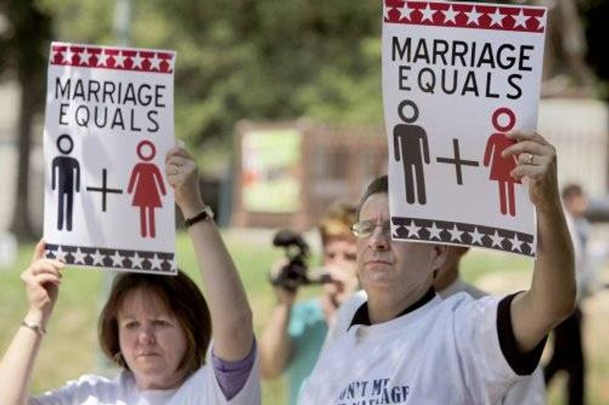 ** FILE ** From left, Martha and Stan Harper hold signs in support of the National Organization for Marriage on Aug. 10, 2010 in Raleigh, North Carolina. (Associated Press)