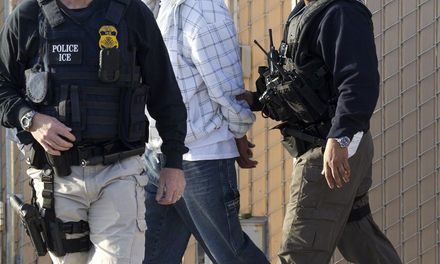 **FILE** Immigration and Customs Enforcement (ICE) agents take a suspect into custody on March 30, 2012, as part of a nationwide immigration sweep in Chula Vista, Calif. (Associated Press)