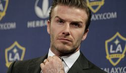 **FILE** Los Angeles Galaxy's David Beckham fixes his tie during a news conference in Los Angeles on Jan. 19, 2012. (Associated Press)