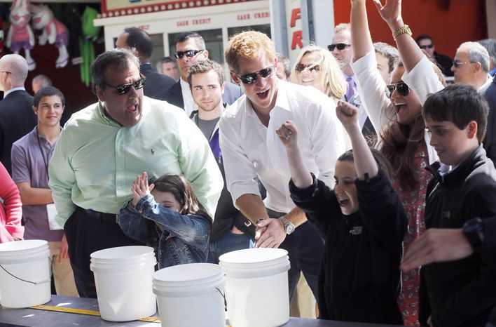 N.J. Gov. Chris Christie and Britain's Prince Harry react as Taylor Cirigliano, 11, of Middletown, N.J. wins a prize playing the Ball Toss game on the boardwalk in Seaside Heights, Tuesday, May 14, 2013. (AP Photo/The Star-Ledger, Andrew Mills, Pool)
