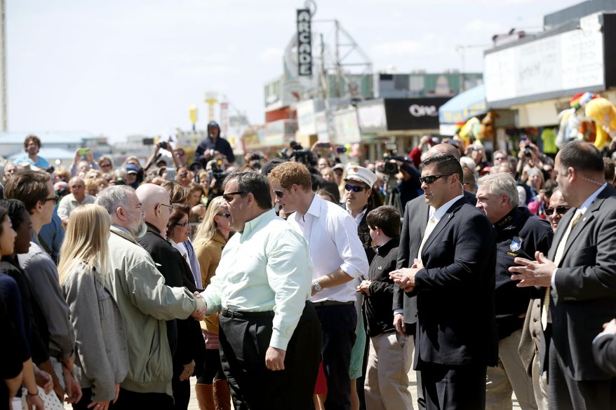 N.J. Gov. Chris Christie and Britain's Prince Harry are greeted by a large crowd as they arrive on the Seaside Heights Boardwalk as they tour areas of Ocean County that suffered extensive damage during Hurricane Sandy on Tuesday, May 14, 2013, in Seaside Heights, N.J. (AP Photo/The Star-Ledger, Andrew Mills, Pool)