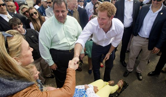 Britain's Prince Harry shakes hands with Mantoloking, N.J., residents as he and N.J. Gov. Chris Christie tour areas of Ocean County that suffered extensive damage during Hurricane Sandy on Tuesday, May 14, 2013. (AP Photo/The Star-Ledger, Andrew Mills, Pool)