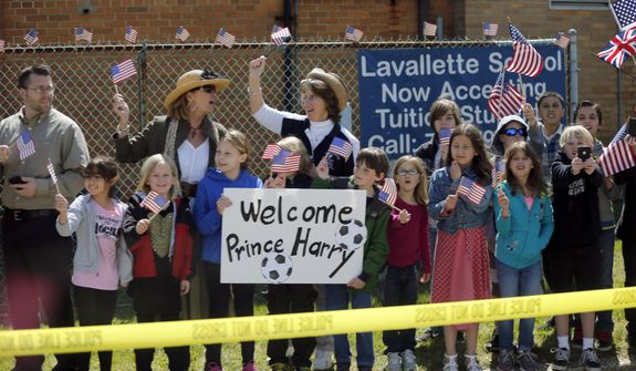 Dozens of students from Lavallette Elementary School line Route 35 as the motorcade of Britain's Prince Harry and N.J. Gov. Chris Christie heads south from Mantoloking to Seaside Heights, N.J., as they tour areas of Ocean County that suffered extensive damage during Hurricane Sandy, Tuesday, May 14, 2013. (AP Photo/The Star-Ledger, Andrew Mills, Pool)