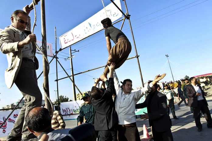 **FILE** In this May 8, 2013, photo released by the Iranian Mehr News Agency, men hold a man hanged in public, to prevent his execution, after he was pardoned by the family of the policeman he was convicted of killing, in Mashhad, northeastern Iran. Under Sharia law, a victim's family has the option to forgive the criminal rather than allowing the perpetrator to be executed. (Associated Press)