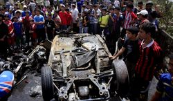 Onlookers gather at the scene of a car bomb attack in the Sadr City neighborhood in Baghdad on Thursday, May 16, 2013. (AP Photo/Karim Kadim)