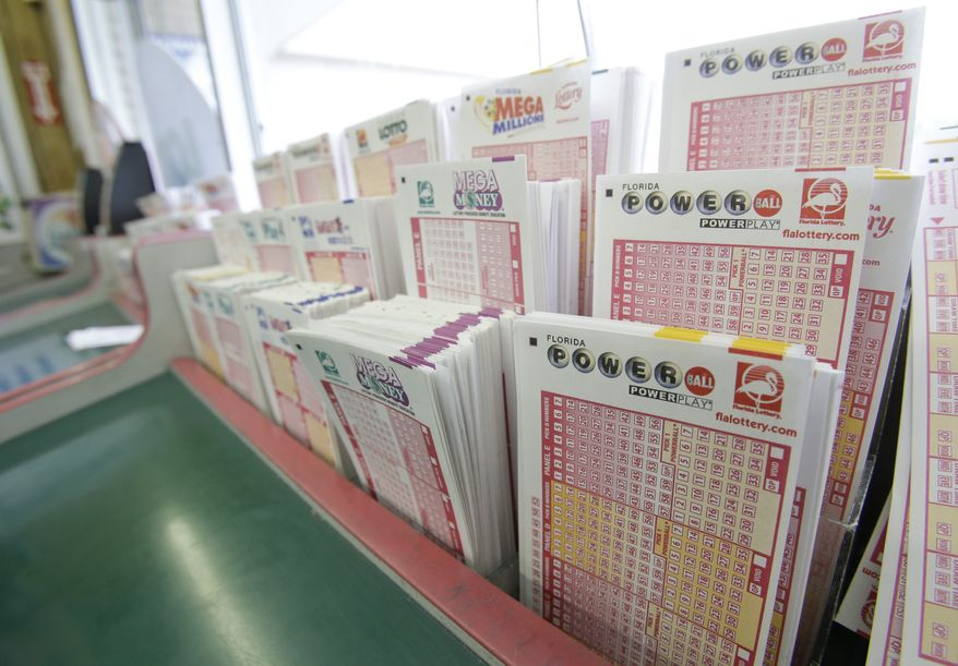 Powerball tickets (right) along with other lotto tickets are seen May 16, 2013, at a convenience store in Orlando, Fla. The prize, estimated around $550 million, is the third largest in lottery history, with the winning numbers to be drawn two days later. (Associated Press)