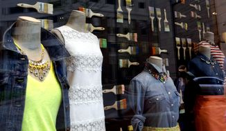 Clothing is displayed on mannequins in a retail store's window in Baltimore on Wednesday, April 24, 2013. (AP Photo/Patrick Semansky)