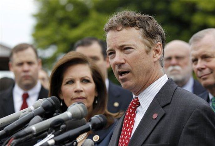 Rep. Michele Bachmann, R-Minn., chairwoman of the Tea Party Caucus, listens at left as while Sen. Rand Paul, R-Ky., speaks during a news conference with Tea Party leaders about the IRS targeting Tea Party groups, Thursday, May 16, 2013, on Capitol Hill in Washington. (Associated Pres