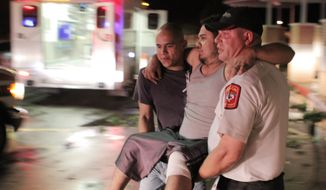 "Johnny Ortiz, left, and James South, right, carry Miguel Morales, center, who was injured in a tornado, to an ambulance in Granbury, Texas, on Wednesday May 15, 2013. Officials report the tornado caused ""multiple fatalities"" as it tore through two neighborhoods of a North Texas town. (AP Photo/Mike Fuentes)"