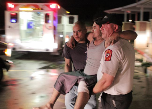 """Johnny Ortiz, left, and James South, right, carry Miguel Morales, center, who was injured in a tornado, to an ambulance in Granbury, Texas, on Wednesday May 15, 2013. Officials report the tornado caused """"multiple fatalities"""" as it tore through two neighborhoods of a North Texas town. (AP Photo/Mike Fuentes)"""